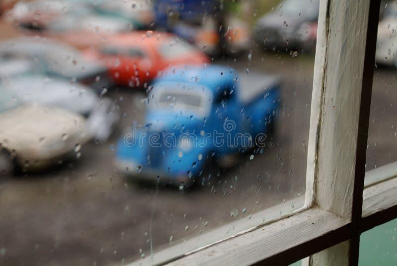 Παλαιό μπλε αυτοκίνητο από ένα παράθυρο στοκ εικόνες