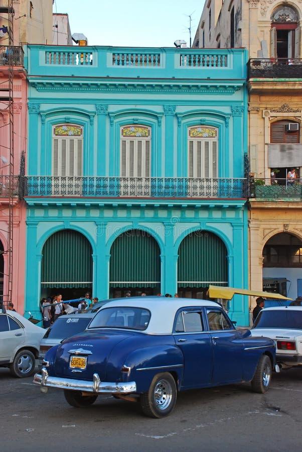 Παλαιό μπλε αυτοκίνητο του Πλύμουθ μπροστά από το ζωηρόχρωμο κτήριο στην Κούβα στοκ φωτογραφία με δικαίωμα ελεύθερης χρήσης