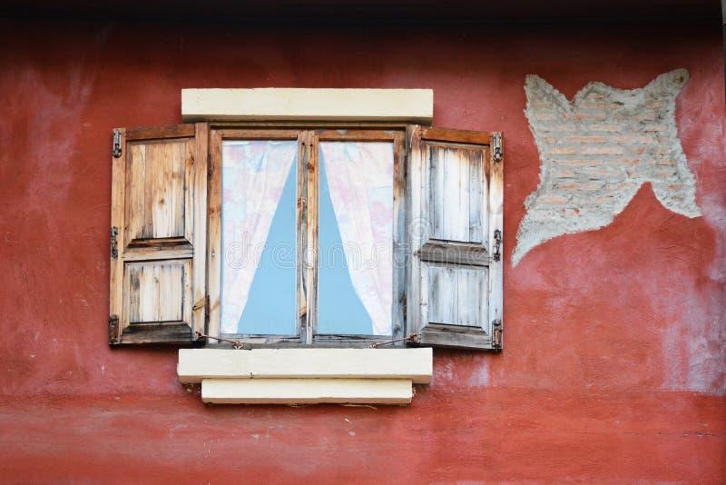 Παλαιό ξύλινο παράθυρο στον κόκκινο τοίχο στοκ εικόνα