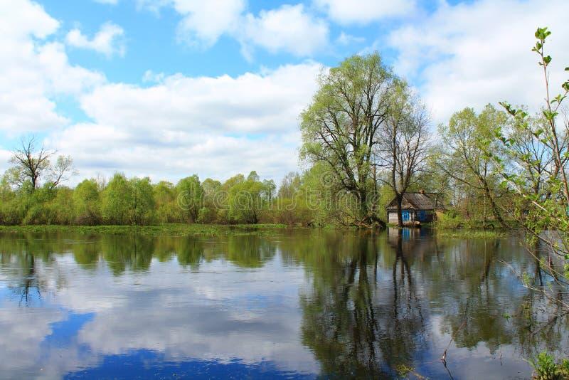 Παλαιό ξύλινο σπίτι που περιβάλλεται από το νερό στοκ φωτογραφία
