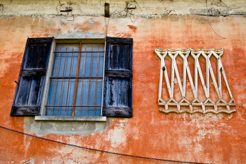 Παλαιό παράθυρο και ξυμένος τοίχος στο αρχαίο σπίτι στοκ εικόνα