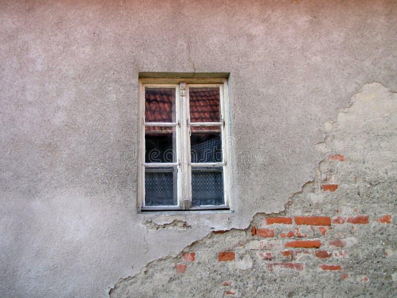 Παλαιό παράθυρο στο χαλασμένο τουβλότοιχο με τις ρωγμές στοκ εικόνες
