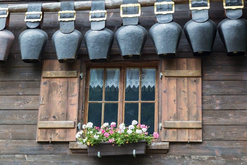 Παλαιό παράθυρο τα ανοικτά παραθυρόφυλλα που διακοσμούνται με με τα λουλούδια και τα κουδούνια στοκ εικόνα