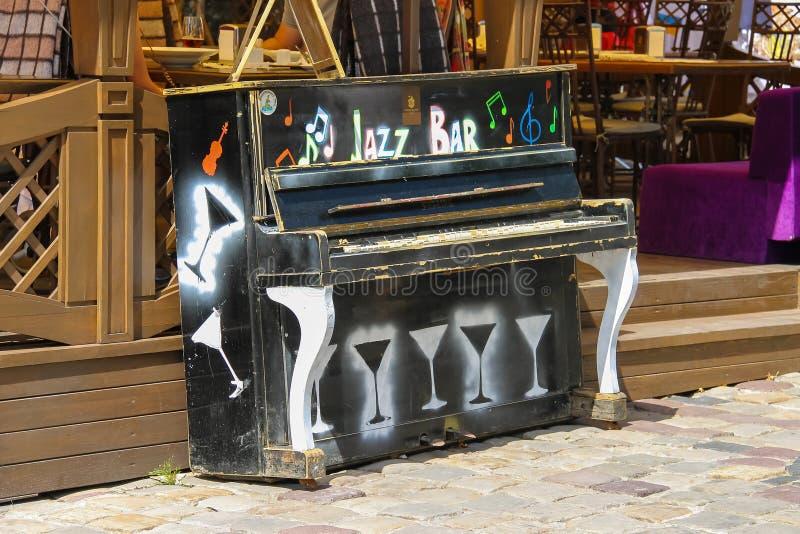 Παλαιό πιάνο κοντά στο υπαίθριο πεζούλι του εστιατορίου στοκ εικόνες