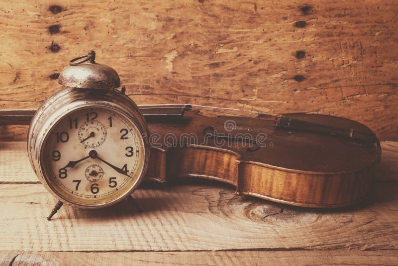 Παλαιό ρολόι και παλαιό βιολί πέρα από τον εκλεκτής ποιότητας ξύλινο πίνακα στοκ φωτογραφία