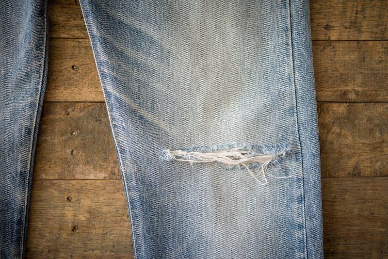 Παλαιό τζιν παντελόνι με σχισμένος στο ξύλινο υπόβαθρο στοκ εικόνα με δικαίωμα ελεύθερης χρήσης