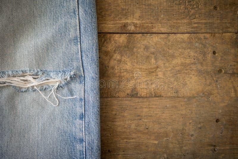 Παλαιό τζιν παντελόνι με τη σχισμένη σύσταση στο ξύλο στοκ εικόνα με δικαίωμα ελεύθερης χρήσης