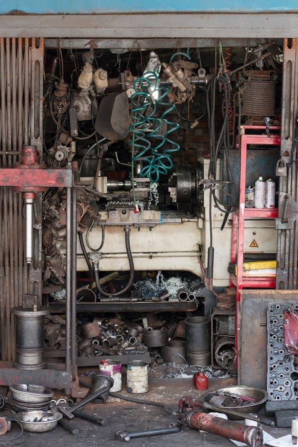 Παλαιό Autoshop με τα μέρη των εργαλείων στο μέτωπο στοκ φωτογραφίες με δικαίωμα ελεύθερης χρήσης