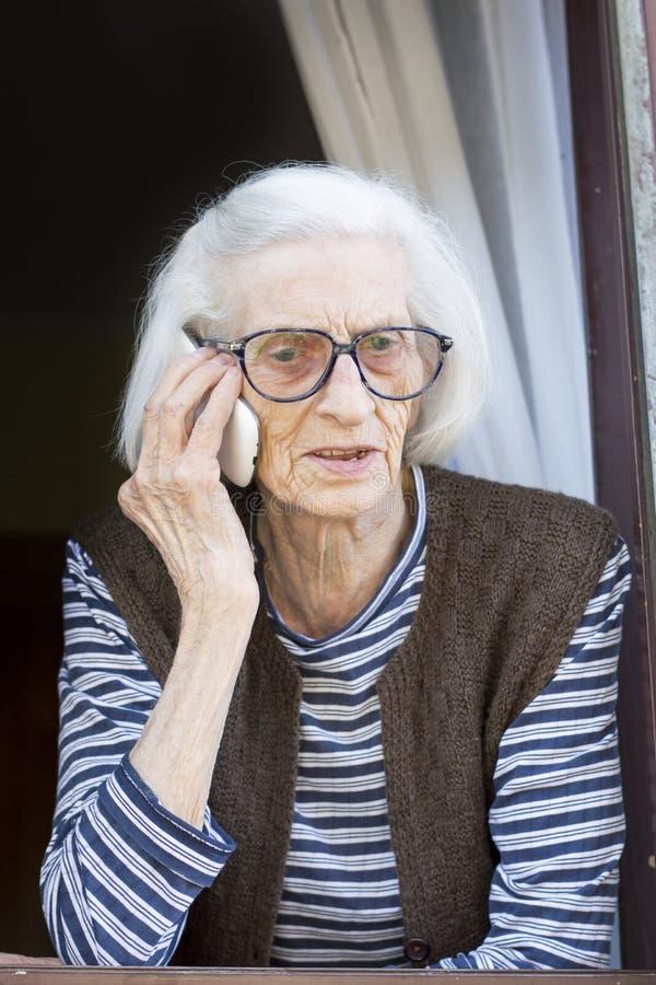 Παλαιό grandma που μιλά στο τηλέφωνο που στέκεται στο παράθυρό της στοκ εικόνες με δικαίωμα ελεύθερης χρήσης