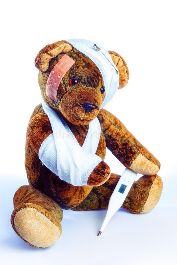 Παλαιό Teddy ως Invalider με το βραχίονα στον επίδεσμο και ένα θερμόμετρο στοκ εικόνα