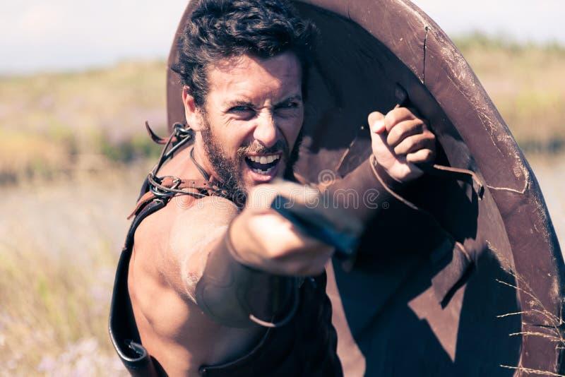 Παλεύοντας αρχαίος πολεμιστής στο τεθωρακισμένο με το ξίφος και την ασπίδα στοκ φωτογραφία με δικαίωμα ελεύθερης χρήσης