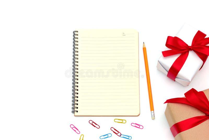 Πεδίο δώρων με το σημειωματάριο, μολύβι κίτρινο, συνδετήρας εγγράφου που τοποθετείται στο γραφείο που απομονώνεται στο άσπρο υπόβ στοκ φωτογραφία με δικαίωμα ελεύθερης χρήσης