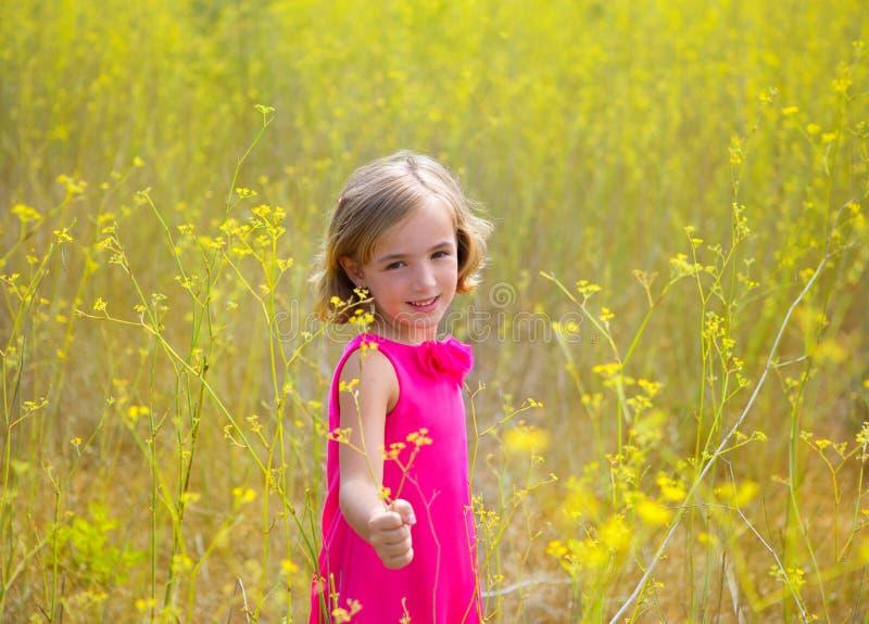 Πεδίο λουλουδιών κοριτσιών παιδιών παιδιών την άνοιξη κίτρινο και ρόδινο φόρεμα στοκ εικόνες