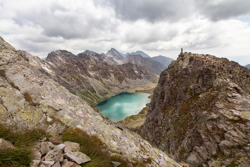 Πεζοπορία γυναίκα που στέκεται στην υψηλή αιχμή και που δείχνει στα δύσκολα βουνά Tatra στοκ φωτογραφία με δικαίωμα ελεύθερης χρήσης