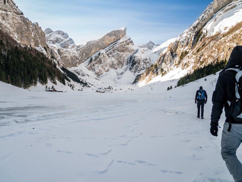 Πεζοπορία πέρα από την παγωμένη λίμνη με το μικρό χωριό, ελβετικά βουνά στοκ φωτογραφίες με δικαίωμα ελεύθερης χρήσης