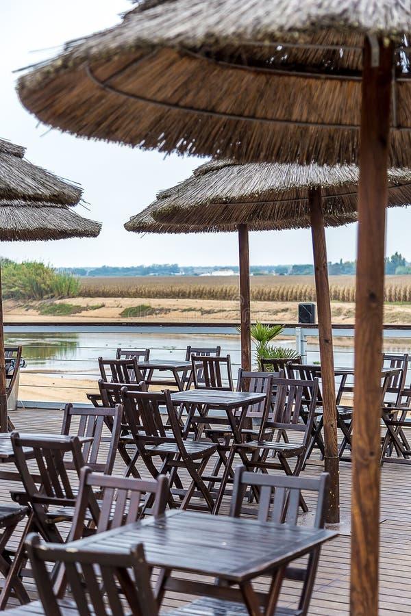 Πεζούλι καφέ από τον ποταμό με τις ξύλινους έδρες και τους πίνακες στοκ εικόνες