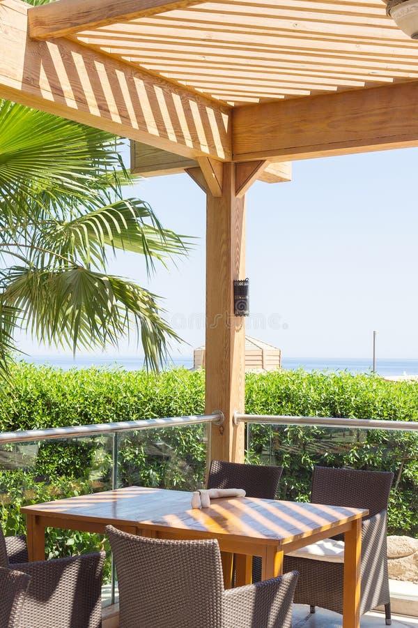 Πεζούλι του εστιατορίου που αγνοεί τη θάλασσα και τους φοίνικες στοκ φωτογραφία