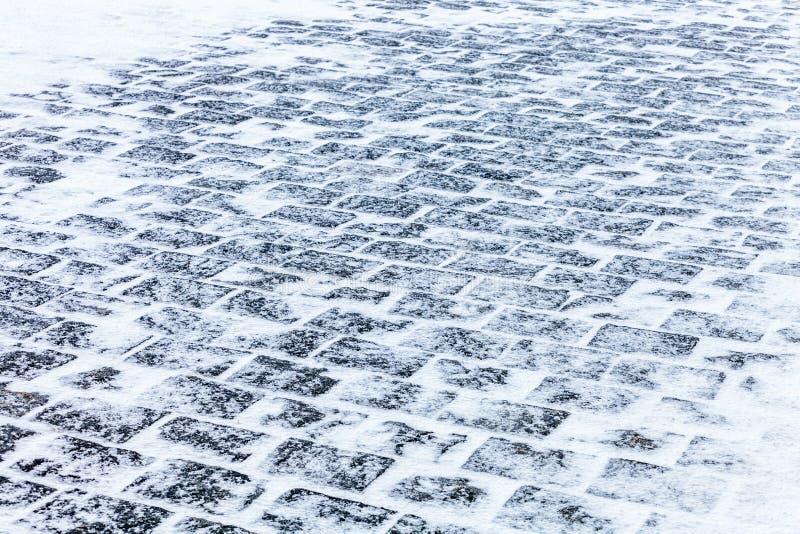 Πεζοδρόμιο κυβόλινθων που καλύπτεται με το χιόνι και τον πάγο στοκ εικόνες