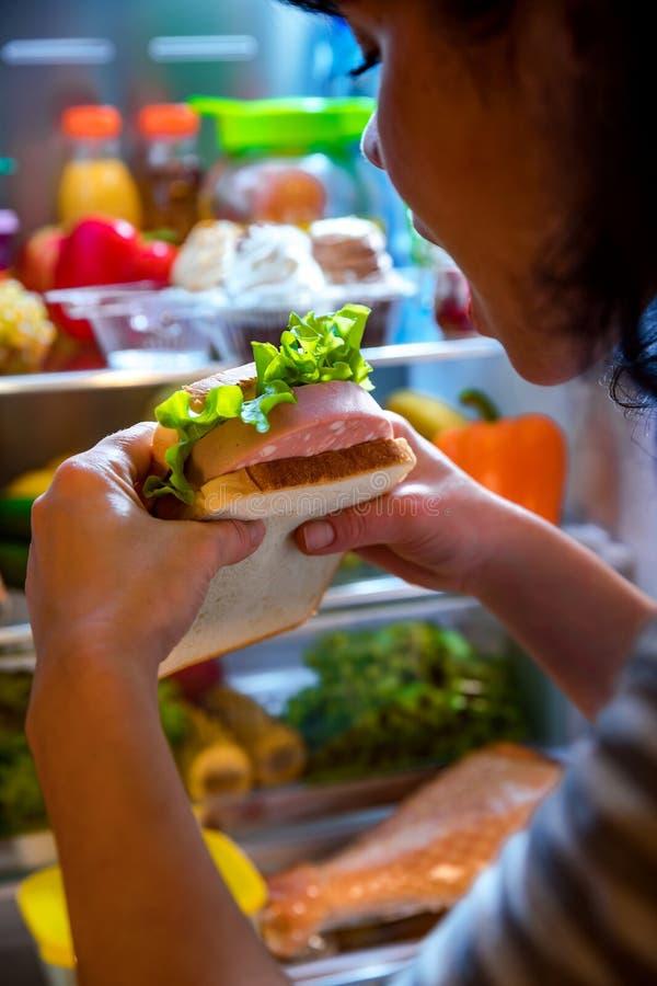 Πεινασμένη γυναίκα που κρατά ένα σάντουιτς στα χέρια του και που στέκεται επόμενο το τ στοκ εικόνα με δικαίωμα ελεύθερης χρήσης