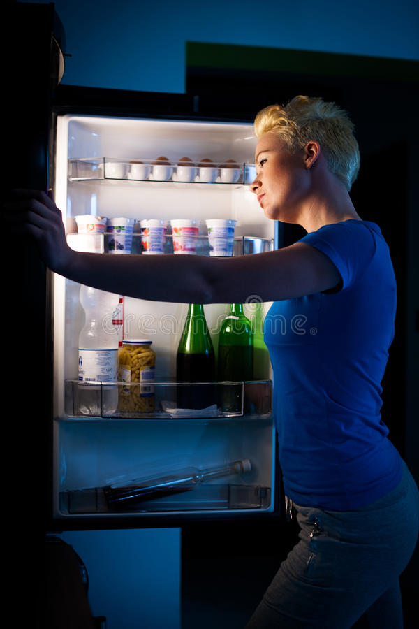 Πεινασμένη γυναίκα που ψάχνει για τα τρόφιμα στο refregirator τη νύχτα στοκ εικόνες