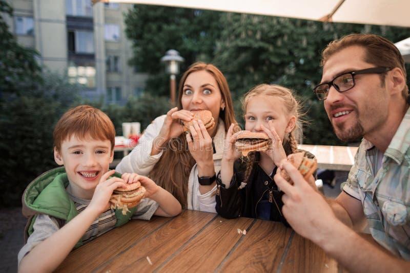 Πεινασμένη οικογένεια που τρώει τα χάμπουργκερ, που κάθονται σε έναν πίνακα σε ένα εστιατόριο γρήγορου φαγητού στοκ φωτογραφίες