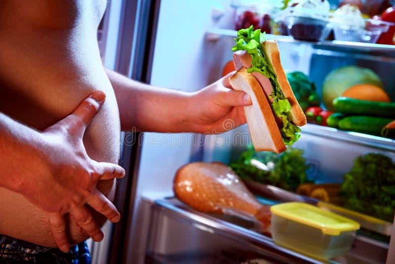 Πεινασμένο άτομο που κρατά ένα σάντουιτς στα χέρια του και που στέκεται δίπλα στοκ φωτογραφία με δικαίωμα ελεύθερης χρήσης
