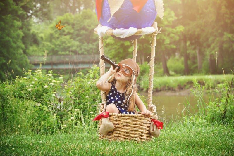 Πειραματικό κορίτσι στο μπαλόνι ζεστού αέρα που προσποιείται να ταξιδεψει στοκ φωτογραφίες με δικαίωμα ελεύθερης χρήσης