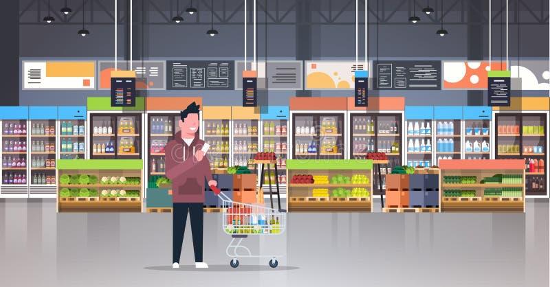 Πελάτης ατόμων υπεραγορών που ελέγχει την αρσενική αγορά παντοπωλείων προϊόντων αγοράς αγοραστών κάρρων καροτσακιών μεταφοράς κατ απεικόνιση αποθεμάτων