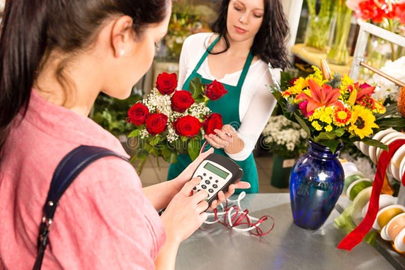 Πελάτης γυναικών που πληρώνει στο ανθοπωλείο την πιστωτική κάρτα στοκ εικόνες με δικαίωμα ελεύθερης χρήσης