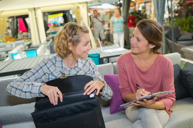 πελάτης και πωλητής 2 γυναικών που συζητούν τον καναπέ τιμών στοκ εικόνες