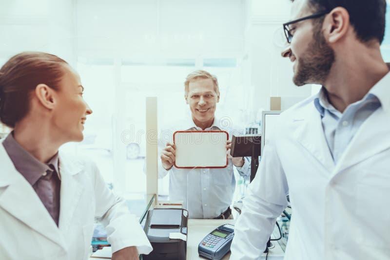 Πελάτης που κρατά μια αφίσσα στο φαρμακείο στοκ εικόνα