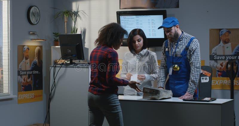 Πελάτης που λαμβάνει τη χαλασμένη συσκευασία στο γραφείο εξυπηρέτηση στοκ εικόνες