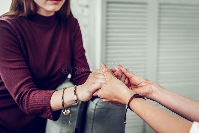 Πελάτης του οικογενειακού θεράποντος που φορά τα σκοτεινά χέρια τινάγματος πουλόβερ στοκ φωτογραφία