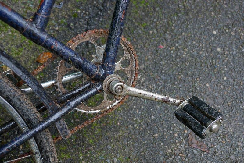 Πεντάλια και αλυσίδα στο πλαίσιο ενός παλαιού ποδηλάτου σε έναν δρόμο ασφάλτου στοκ φωτογραφίες