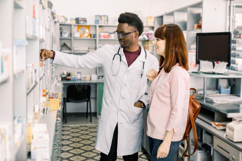 Πεπειραμένος φαρμακοποιός ατόμων αφροαμερικάνων που συμβουλεύεται το θηλυκό πελάτη στο σύγχρονο φαρμακείο στοκ φωτογραφία