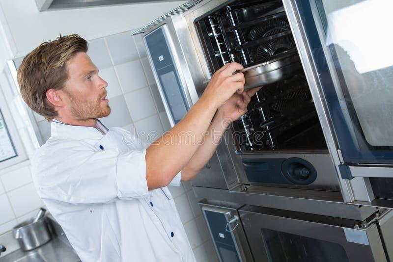Πεπειραμένος όμορφος αρχιμάγειρας που βάζει το πιάτο στο φούρνο στοκ εικόνες