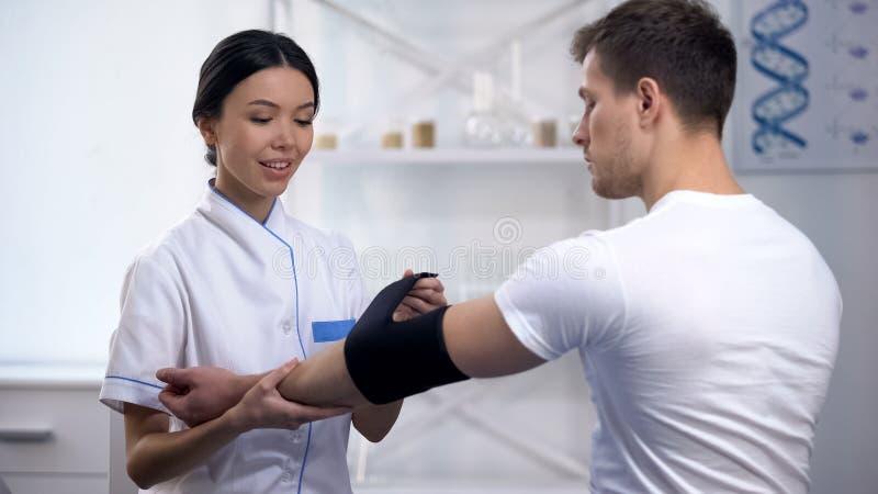 Πεπειραμένο θηλυκό orthopedist που εφαρμόζει γεμισμένο τον αγκώνας ασθενή αθλητικών τύπων όρθωσης στοκ εικόνα