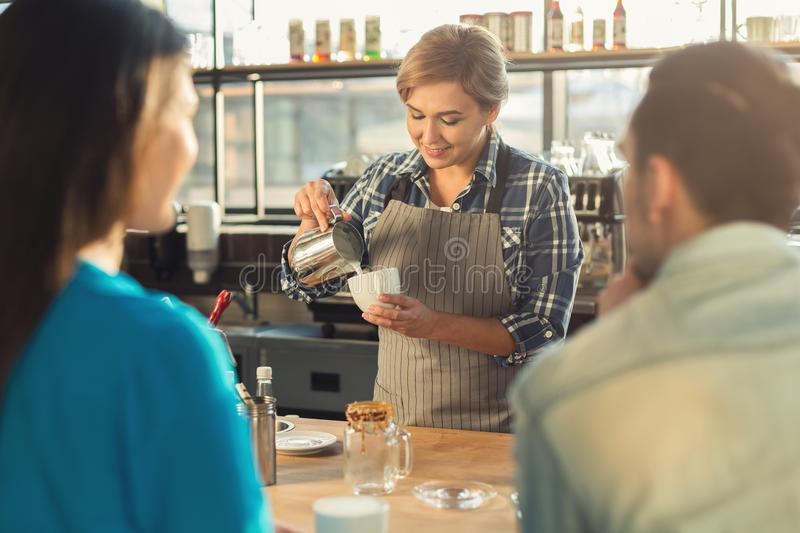 Πεπειραμένο barista χαμόγελου που κατασκευάζει τον καφέ στους πελάτες στοκ φωτογραφίες