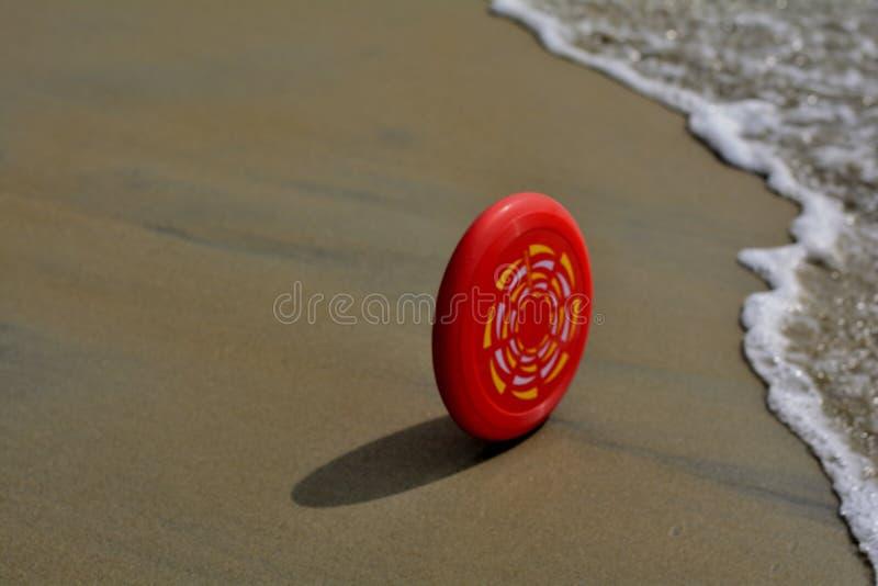 Πεπρωμένο: Frisbee στη δράση - που φθάνει στα κύματα στοκ φωτογραφία
