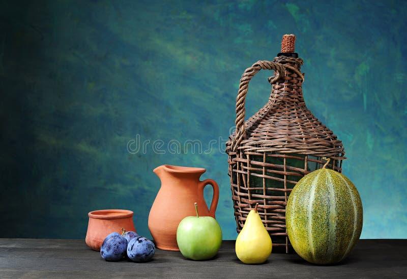 Πεπόνι, αχλάδι, μήλο, δαμάσκηνο και κεραμικά πιάτα στοκ εικόνα