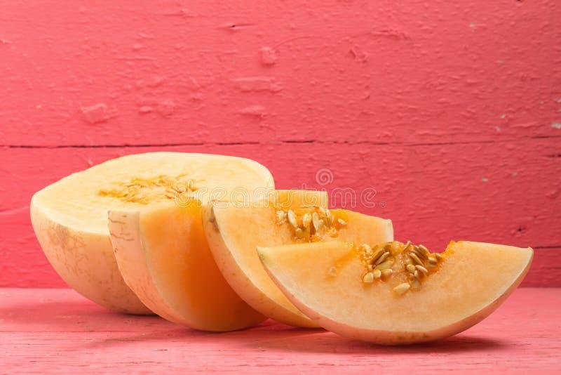 πεπόνι & x28 sunlady& x29  φέτα μισός στο ξύλινο ροζ στοκ φωτογραφία