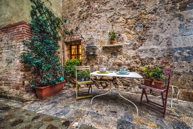 Περίεργη γωνία με τον πίνακα και καρέκλες σε Monteriggioni στοκ φωτογραφίες με δικαίωμα ελεύθερης χρήσης