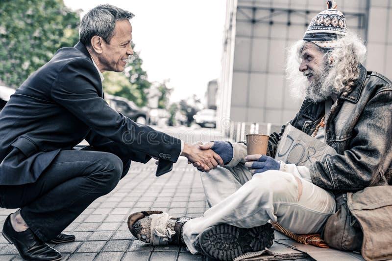 Περίεργη με κοντά μαλλιά συνεδρίαση επιχειρηματιών μπροστά από τους μακρυμάλλεις αστέγους στοκ φωτογραφία με δικαίωμα ελεύθερης χρήσης