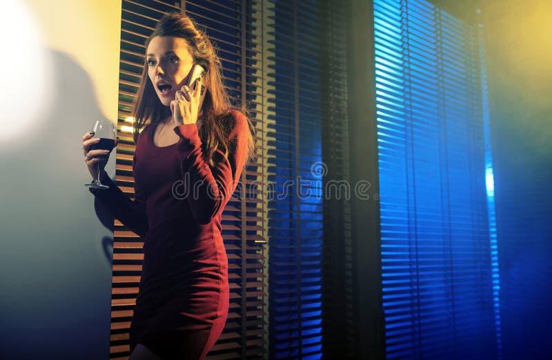Περίεργη νέα γυναίκα που μιλά στο τηλέφωνο κυττάρων στοκ φωτογραφία