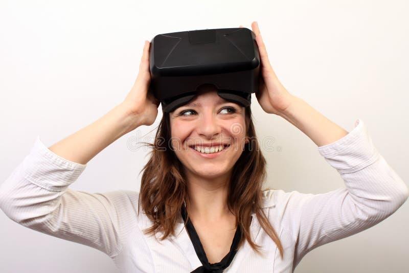 Περίεργη, χαμογελώντας γυναίκα σε ένα άσπρο πουκάμισο, απογειωμένος ή βάζοντας στην τρισδιάστατη κάσκα εικονικής πραγματικότητας  στοκ εικόνα με δικαίωμα ελεύθερης χρήσης