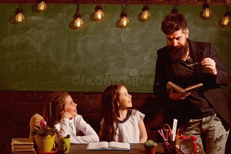 Περίεργος εύθυμος ακούοντας δάσκαλος παιδιών με την προσοχή Μαθητές δασκάλων και κοριτσιών στην τάξη, πίνακας κιμωλίας επάνω στοκ εικόνες