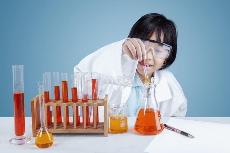 Περίεργο κορίτσι που κάνει τη χημική έρευνα στοκ φωτογραφία