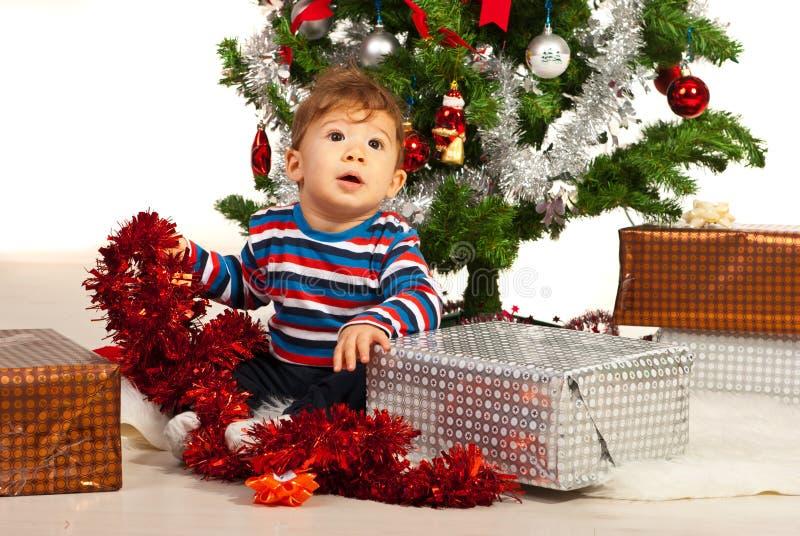 Περίεργο μωρό μπροστά από το χριστουγεννιάτικο δέντρο στοκ φωτογραφίες με δικαίωμα ελεύθερης χρήσης
