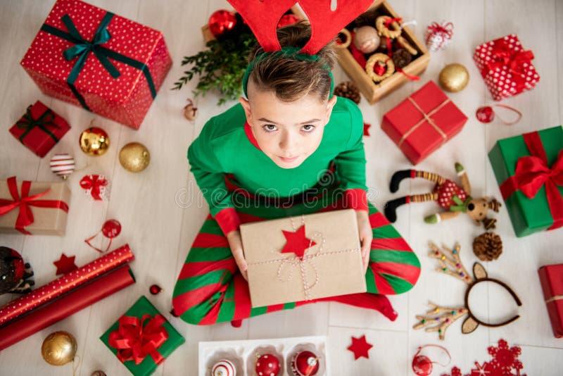 Περίεργο νέο αγόρι που φορά τις πυτζάμες Χριστουγέννων που κάθονται στο πάτωμα, που ανοίγει το χριστουγεννιάτικο δώρο του, τοπ άπ στοκ φωτογραφίες