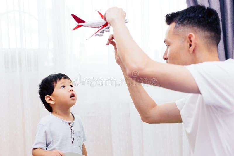 Περίεργο παιδί που εξετάζει το παιχνίδι αεροπλάνων και που παίζει με τον πατέρα Ασιατικά παιχνίδια οικογενειακού παιχνιδιού μαζί  στοκ εικόνες